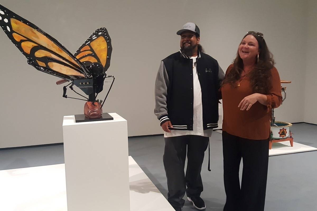 "Labor of Love's Natasha and Ali pose with ""Resurrection,"" their metal and resin butterfly, on view in Yerba Buena Center for the Arts' exhibition ""Art of Peace."" (Leslie Katz/S.F. Examiner)"