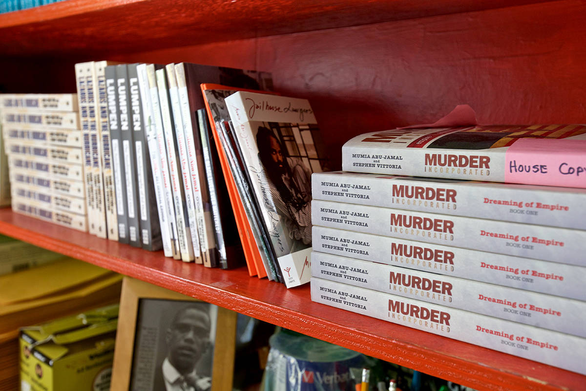 "Copies of ""Murder Incorporated,"" co-written by Mumia Abu-Jamal, sit on a shelf at Prison Radio. (Kevin N. Hume/S.F. Examiner)"
