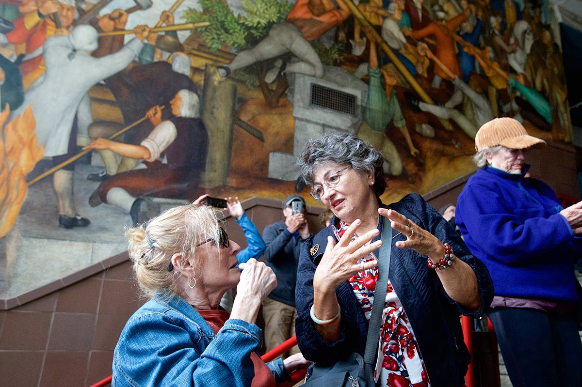 Art historian Marilou Wood, left, and Margaret Herzen, a 1965 graduate of George Washington High School, discuss controversial Works Progress Administration murals that date to the Great Depression at the school on Thursday, Aug. 1, 2019. (Kevin N. Hume/S.F. Examiner)