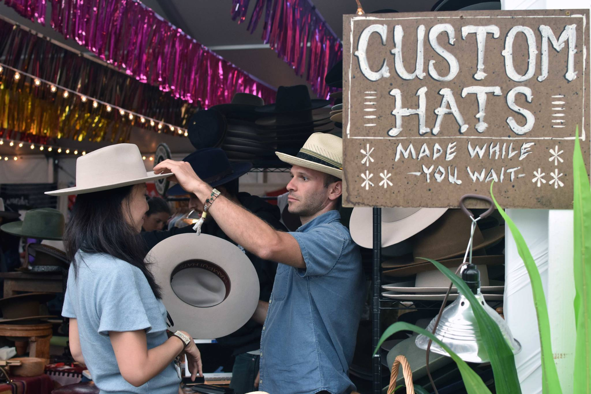 A person tries on hats at the market place at Outside Lands Festival on Saturday, August 10, 2019. (Lola Chase/ Special to S.F. Examiner)