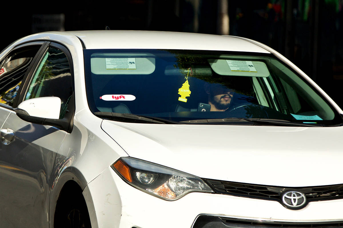 A driver picks up a passenger on Mission Street. (Kevin N. Hume/S.F. Examiner)