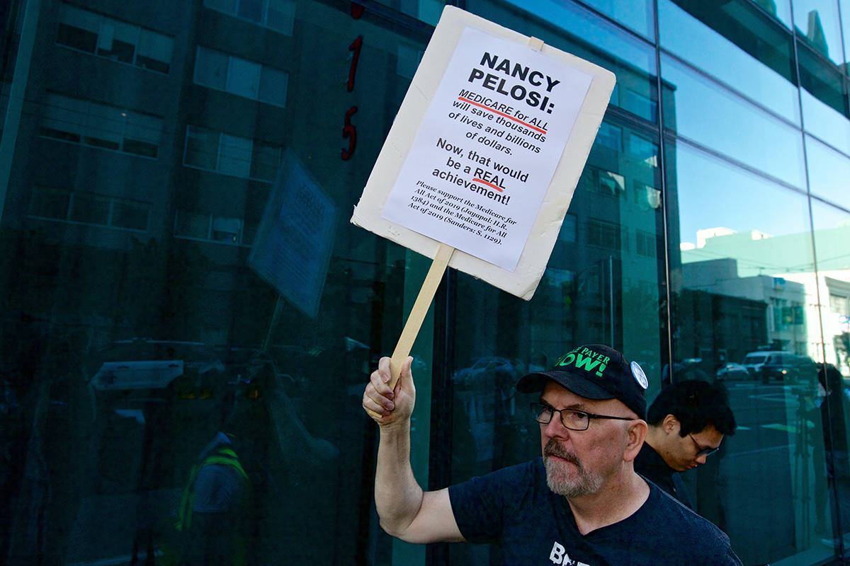 Rick St. John of San Francisco holds a sign as protesters demonstrate outside The InterContinental hotel, where Speaker Nancy Pelosi was receiving a Lifetime Achievement award from the SF Democratic Party, in the South of Market neighborhood on Wednesday, Aug. 21, 2019. (Kevin N. Hume/S.F. Examiner)