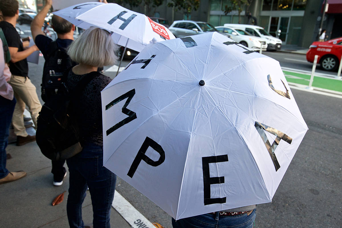 "Two women hold umbrella with letters that spell ""impeach"" on top as protesters demonstrate outside The InterContinental hotel, where Speaker Nancy Pelosi was receiving a Lifetime Achievement award from the SF Democratic Party, in the South of Market neighborhood on Wednesday, Aug. 21, 2019. (Kevin N. Hume/S.F. Examiner)"