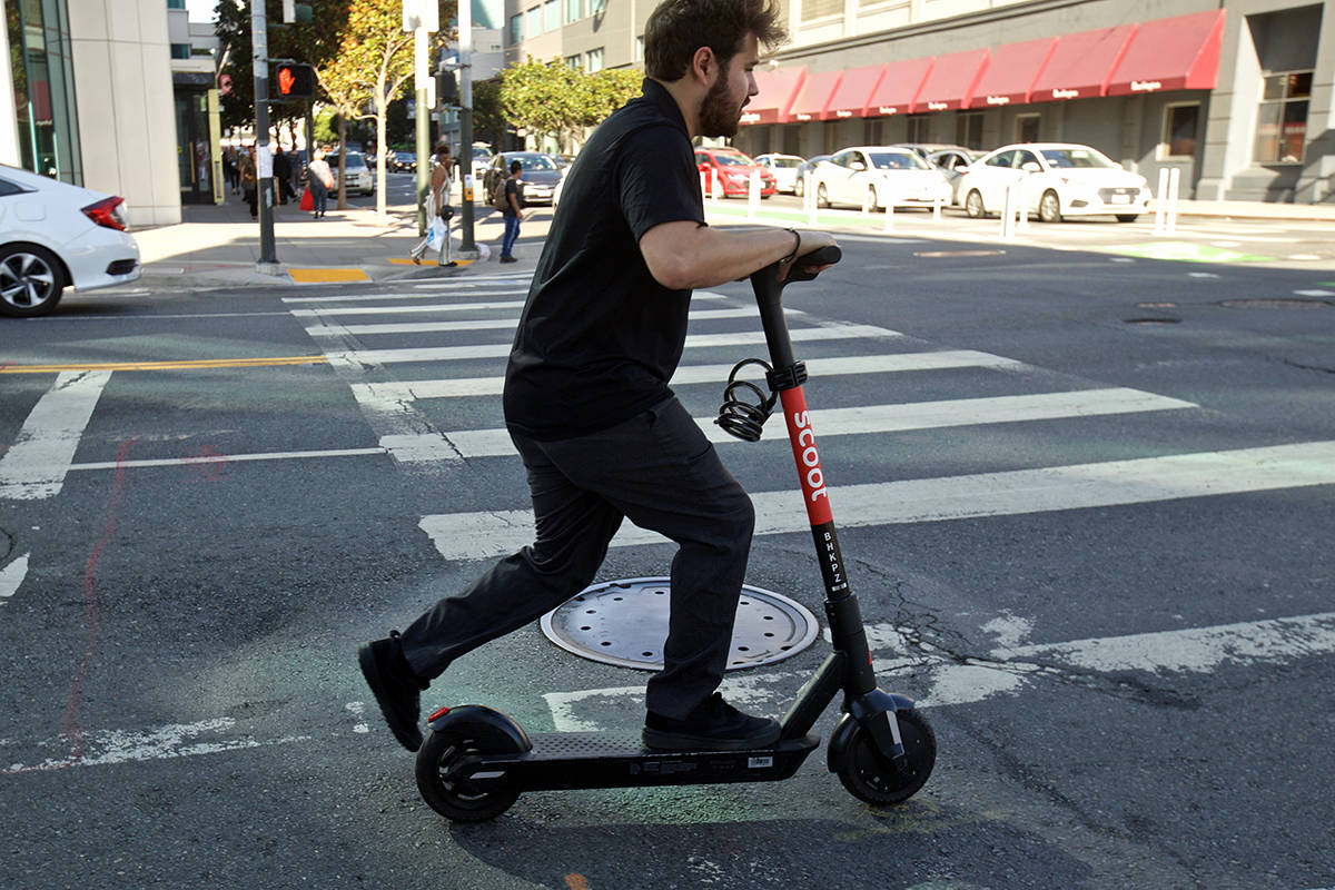 A man kicks off to cross the intersection at Fifth and Howard streets on a Scoot e-scooter on Wednesday, Sept. 25, 2019. The SFMTA voted Wednesday to expand the e-scooter permit program to allow four companies to rent out up to 10,000 e-scooters citywide. (Kevin N. Hume/S.F. Examiner)