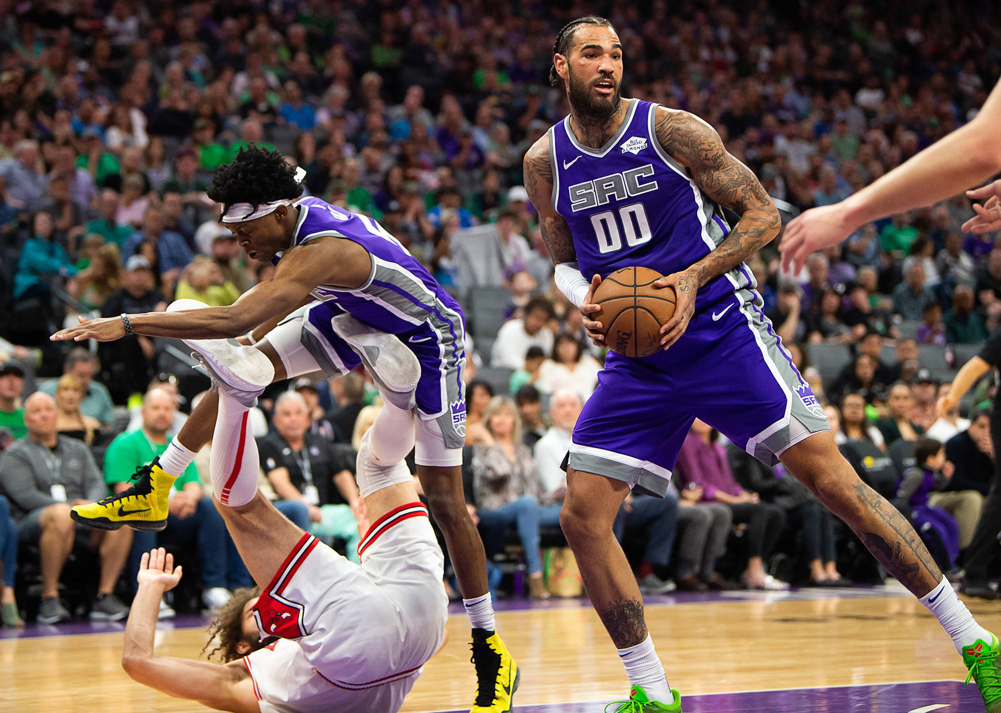 Sacramento Kings center Willie Cauley-Stein (00) grabs the ball from Chicago Bulls center Robin Lopez (42) as Sacramento Kings guard De'Aaron Fox (5) leaps over him on Sunday, March 17, 2019 at Golden 1 Center in Sacramento, Calif. (Paul Kitagaki Jr./Sacramento Bee/TNS)