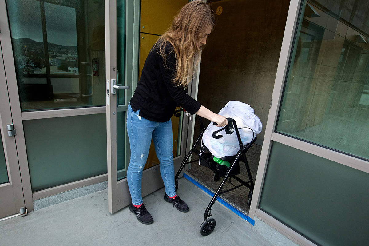 Resident Mary Rocus holds open a door to a balcony as she pushes her walker up over a concrete threshold at the Plaza Apartments at 988 Howard St. on Wednesday, Nov. 27, 2019. (Kevin N. Hume/S.F. Examiner)