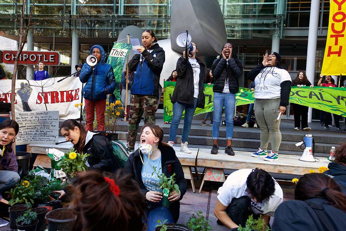 Young climate protesters chant as they plant flowers and paint a message outside the SF headquarters of BlackRock, an investment management corporation, to urge the corporation to divest its funds from fossil fuel companies on Friday, Dec. 6, 2019. (Kevin N. Hume/S.F. Examiner)