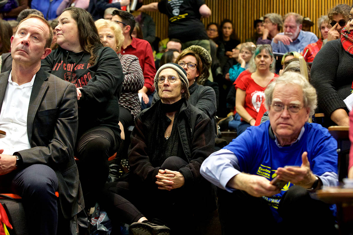 People sit in the aisles during public comment about cuts to classes, particularly those for older adults, at the City College of San Francisco Board of Trustees meeting on Thursday, Dec. 12, 2019. (Kevin N. Hume/S.F. Examiner)