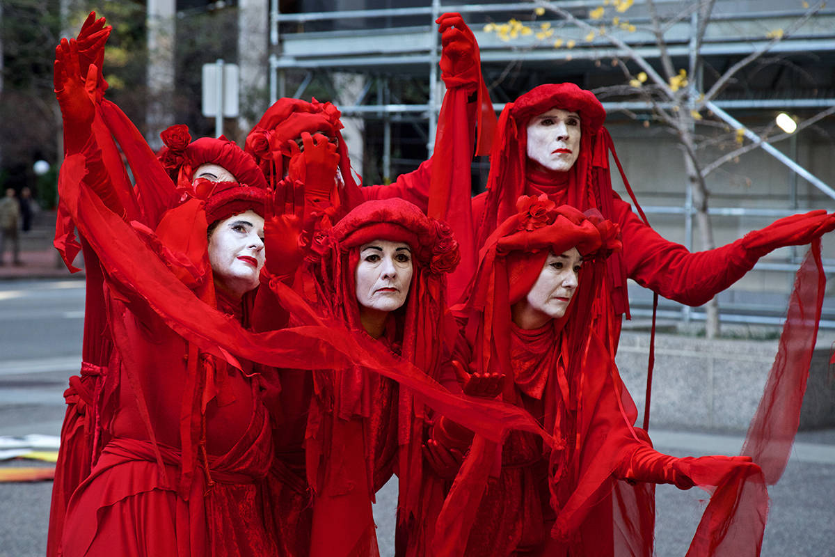 Members of the Extinction Rebellion Red Brigade demonstrate outside PG&E headquarters in downtown SF to call on Gov. Gavin Newsom to turn the company into a public utility on Monday, Dec. 16, 2019. (Kevin N. Hume/S.F. Examiner)