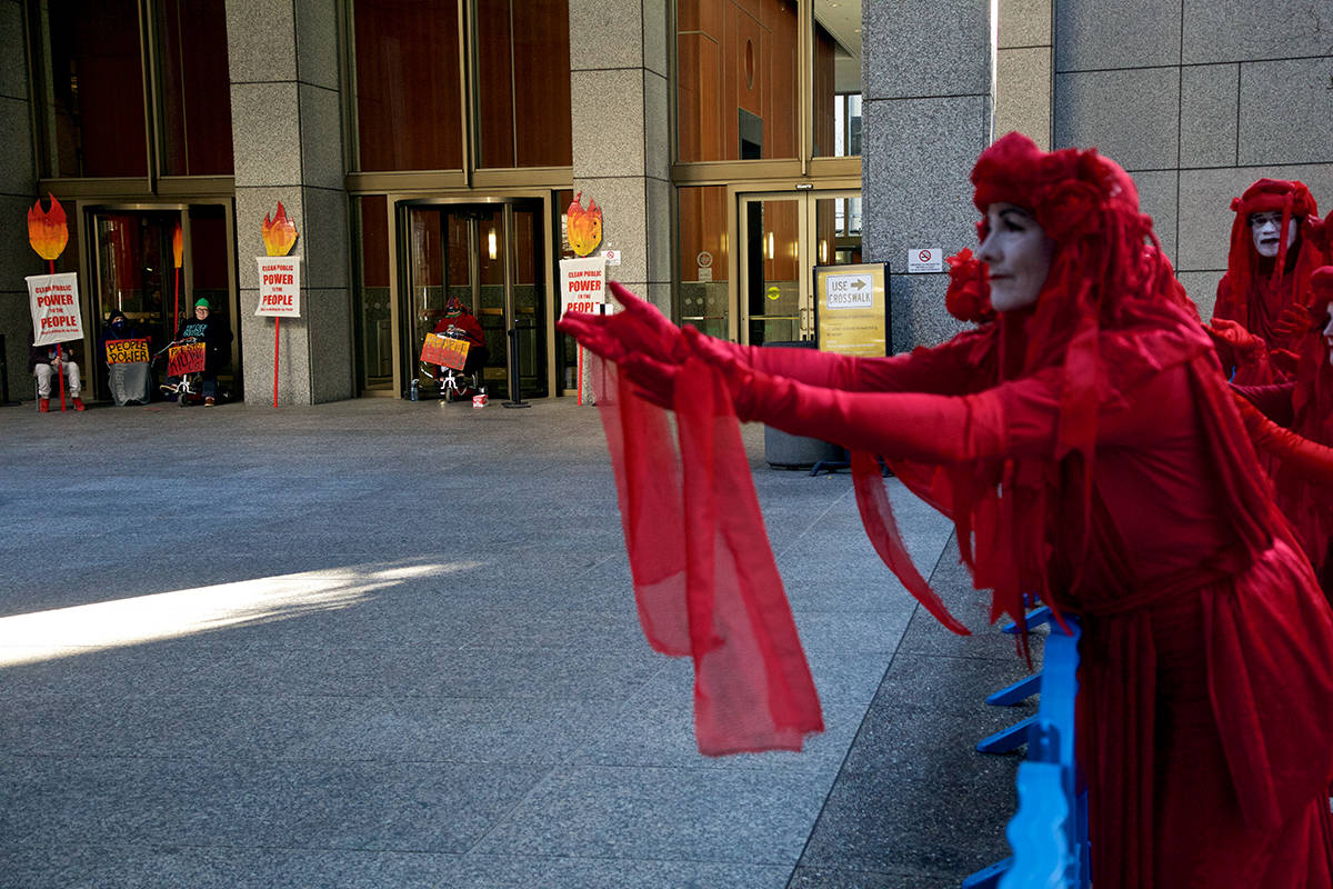 Members of the Extinction Rebellion Red Brigade demonstrate outside PG&E headquarters in downtown SF as protesters block the entrances to call on Gov. Gavin Newsom to turn the company into a public utility on Monday, Dec. 16, 2019. (Kevin N. Hume/S.F. Examiner)