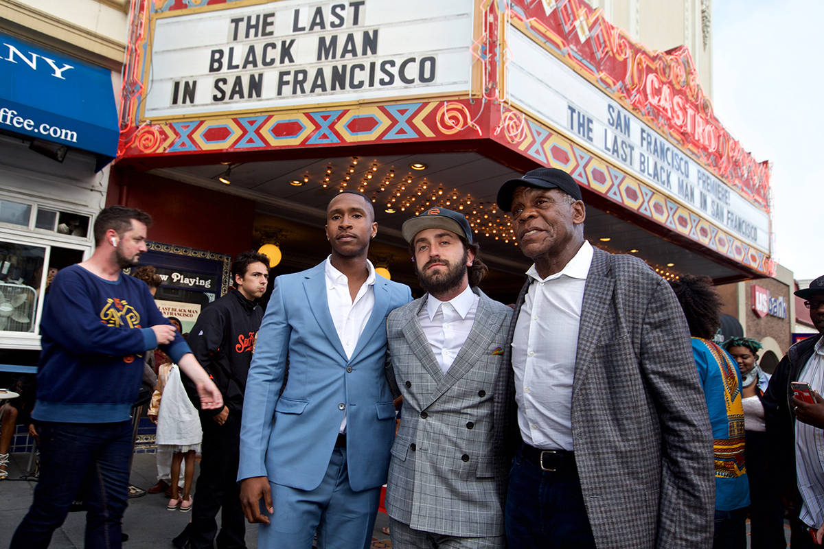"""Actor Jimmie Fails, writer-director Joe Talbot and actor Danny Glover smile for photos under the marquee at the San Francisco premiere of """"The Last Black Man in San Francisco"""" at the Castro Theater on Wednesday, May 29, 2019. (Kevin N. Hume/S.F. Examiner)"""