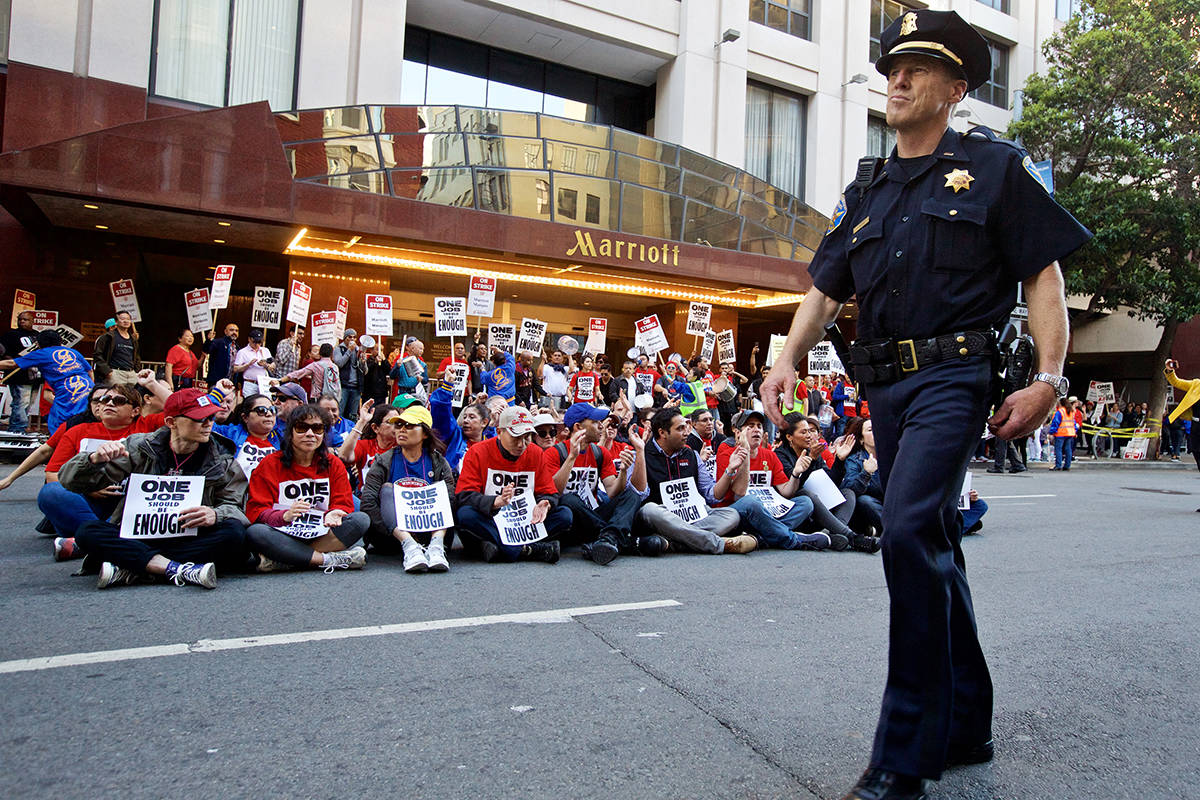 A San Francisco Police officer walks in front of striking workers sitting in the street out in front of the SF Marriott Marquis Hotel on Oct. 12, 2018. (Kevin N. Hume/S.F. Examiner)