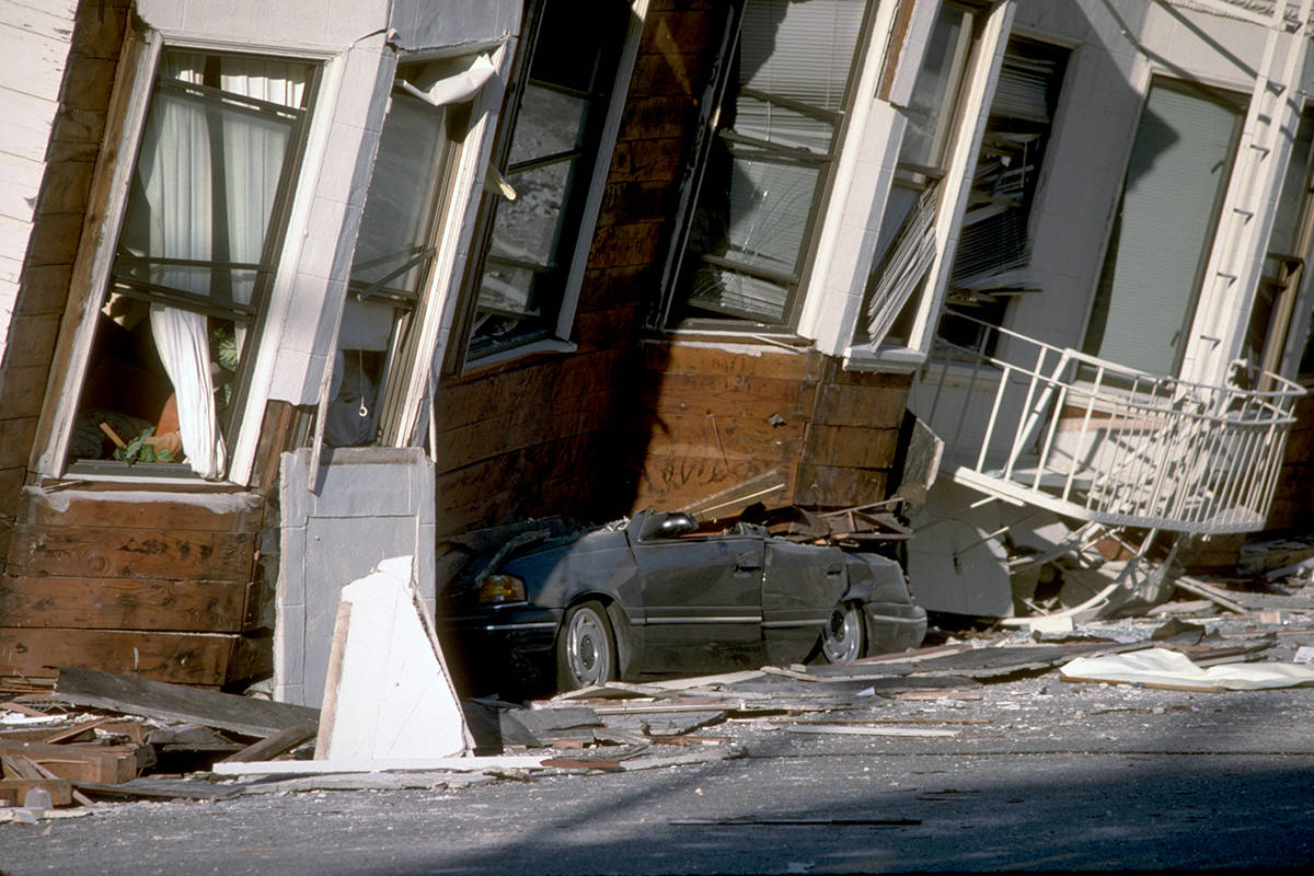 A car lies crushed under the third story of an apartment building in the Marina District that was damaged by the Oct. 17, 1989 Loma Prieta earthquake. (Courtesy U.S. Geological Survey)