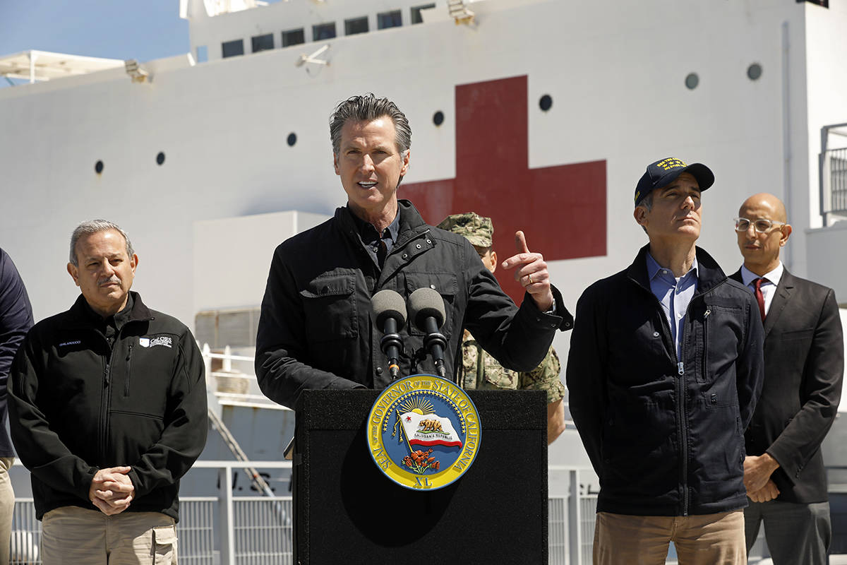 LOS ANGELES, CALIFORNIA-MARCH 27, 2020-California Governor Gavin Newsom speaks in front of the hospital ship USNS Mercy that arrived into the Port of Los Angeles on Friday, March 27, 2020, to provide relief for Southland hospitals overwhelmed by the coronavirus pandemic. Also attending the press conference were Director Mark Ghilarducci, Cal OES, left, Los Angeles Mayor Eric Garcetti, second from right, and Dr. Mark Ghaly, Secretary of Health and Human Services, far right, along with others not shown. (Carolyn Cole/Los Angeles Times/POOL/TNS)
