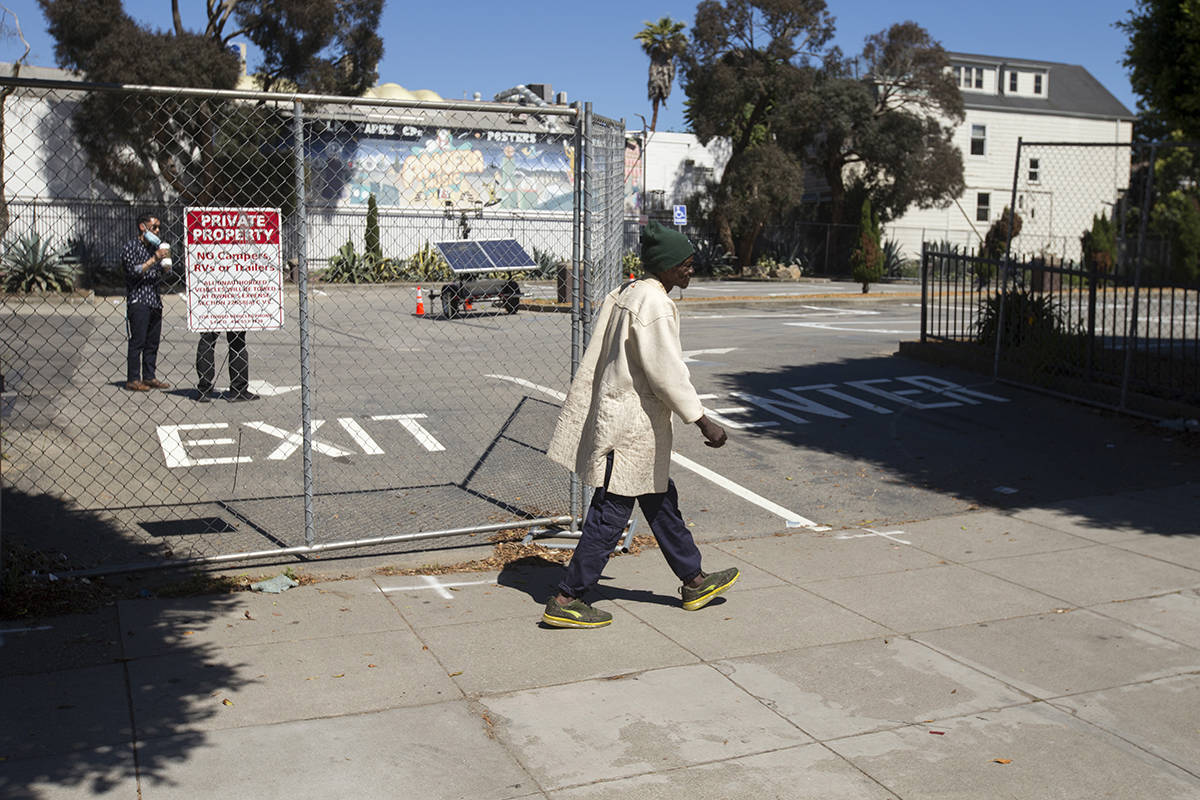 A man walks past the soon-to-open sanctioned camping site for the homeless at the former McDonald's by Golden Gate Park in the Haight on Tuesday, May 26, 2020. (Kevin N. Hume/S.F. Examiner)