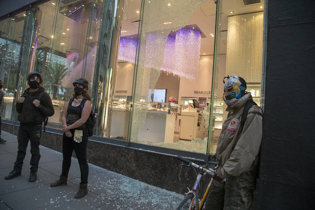 Protesters stand guard outside the Swarovski store at Union Square to prevent looting after someone broke a window. (Kevin N. Hume/S.F. Examiner)