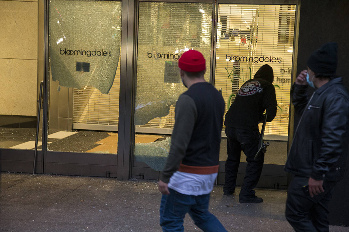 """A protester spray paints the words """"kill cops"""" on the vandalized windows of Bloomingdales at the Westfield Mall on Mission Street during a protest over the Minneapolis police killing of George Floyd on Saturday. (Kevin N. Hume/S.F. Examiner)"""