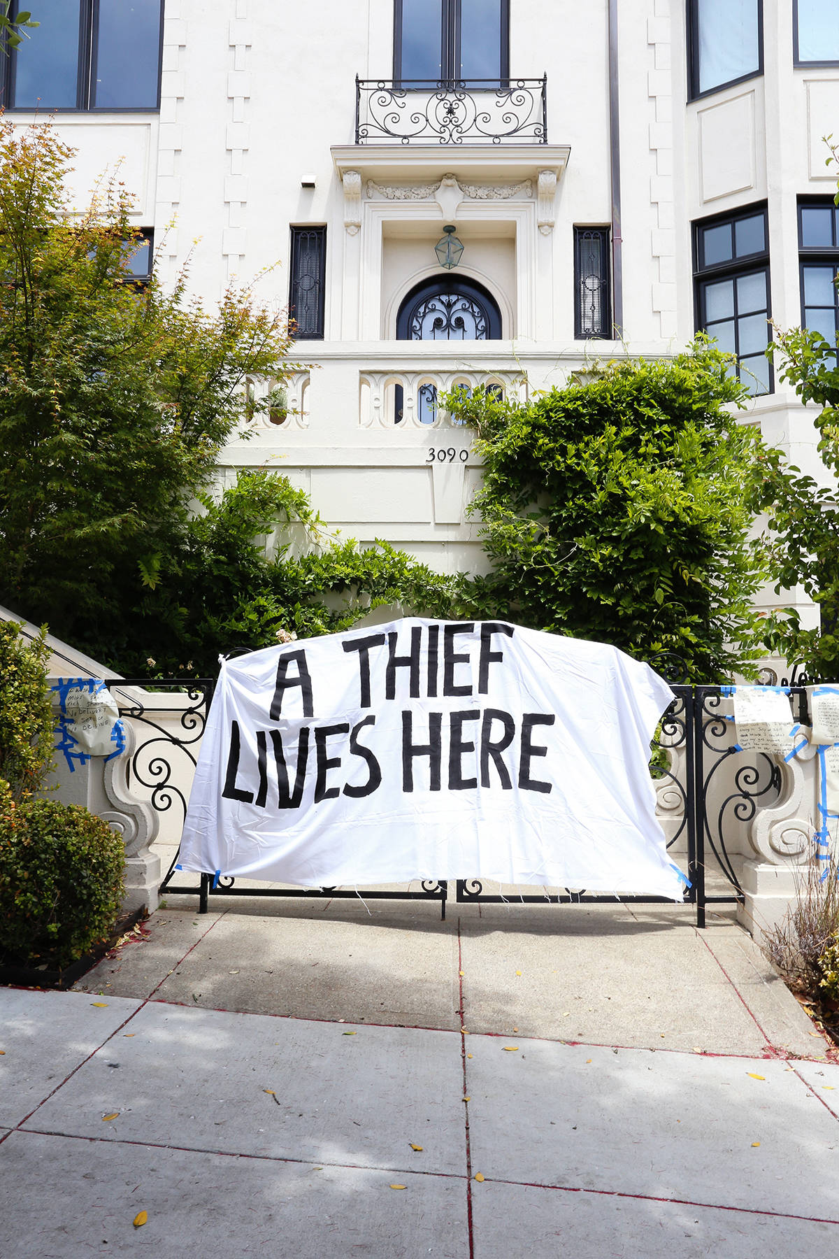 Demonstrators left a banner hanging on the gate of Uber CEO Dara Khosrowshahi's Pacific Heights home on Wednesday, June 24, 2020. (Shandana Qazi/Special to S.F. Examiner)