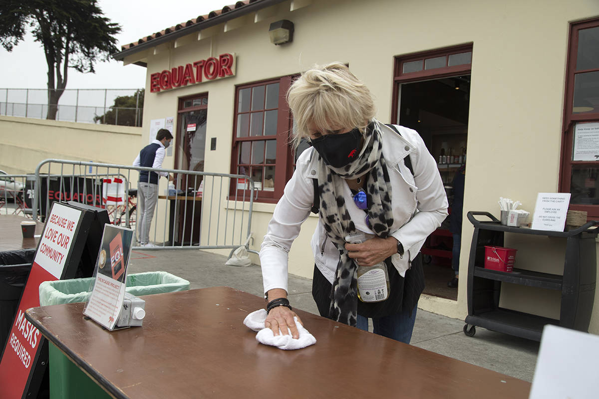 Equator Coffees co-founder and CEO Helen Russell cleans a table where patrons pick up their orders outside the company's Fort Mason Center location on Friday, July 31, 2020. (Kevin N. Hume/S.F. Examiner)