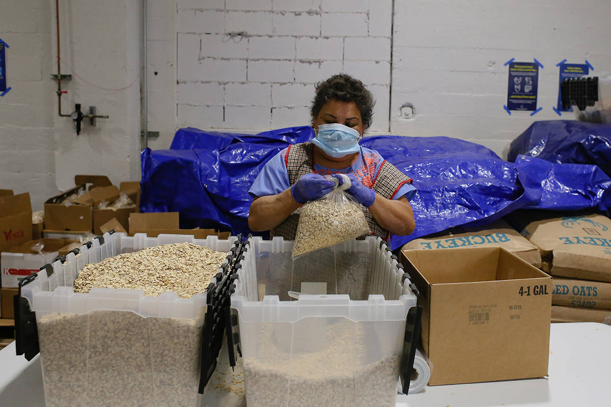 A volunteer packs oats into bags for food boxes for those in need at Mission Food Hub on Friday, July 31, 2020. (Shandana Qazi/Special to the S.F. Examiner)