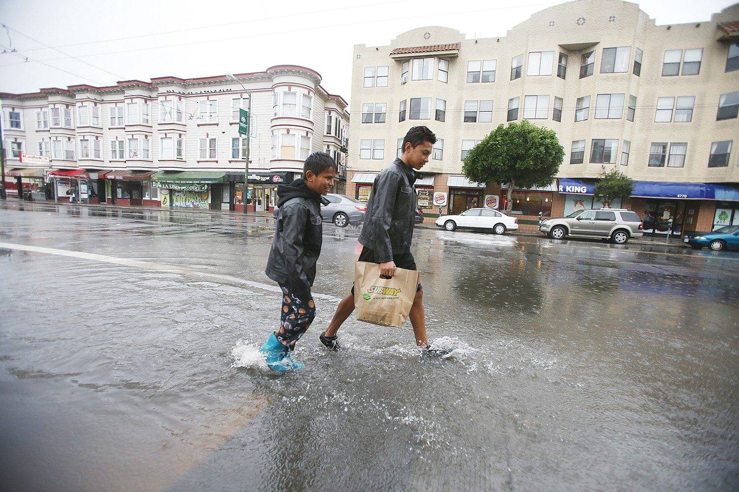 Two boys who had the day off from school due to a storm trudge through the water on Mission Street at Russia Avenue. (Mike Koozmin/2014 SF Examiner file photo)