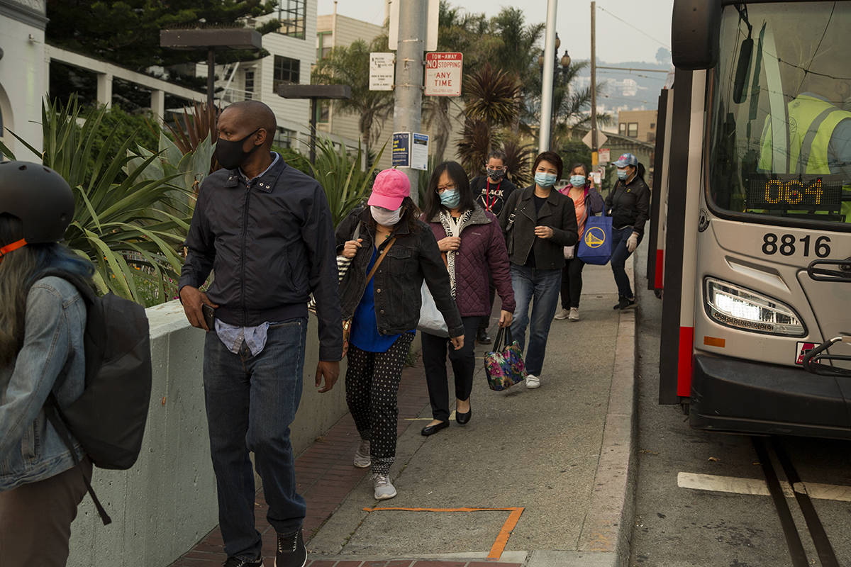 Riders disembark from a Muni Shuttle bus on Monday. The SFMTA plans to continue to serve train routes with buses while it works to get trains back online. (Kevin N. Hume/S.F. Examiner)