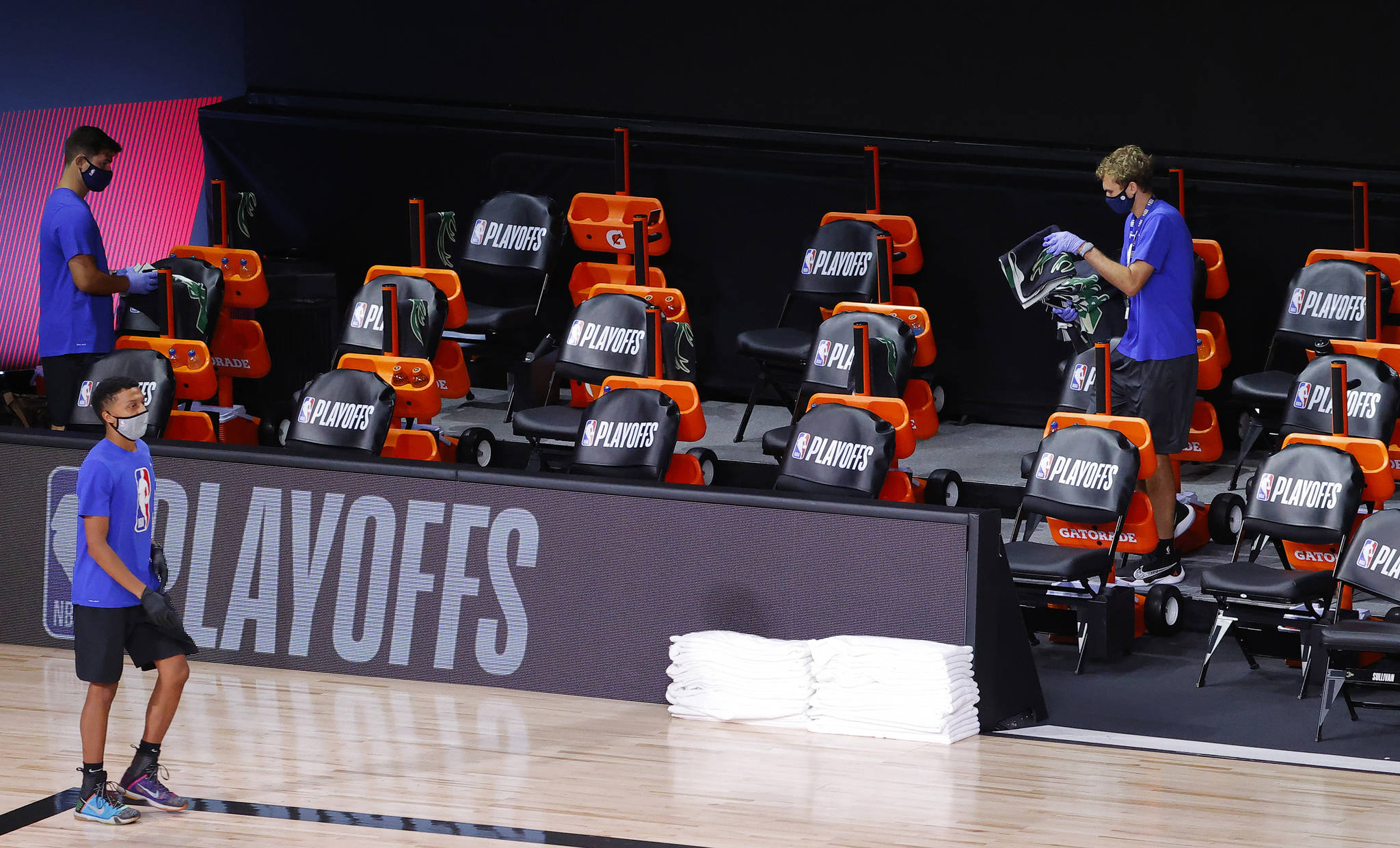 Workers remove towels from the Milwaukee Bucks empty bench after the Bucks sit out Game Five of the Eastern Conference First Round in protest during the 2020 NBA Playoffs against the Orlando Magic at AdventHealth Arena at ESPN Wide World Of Sports Complex on Aug. 26, 2020 in Lake Buena Vista, Florida. The Bucks are boycotting the game to protest the police shooting of Jacob Black. (Kevin C. Cox/Getty Images/TNS)
