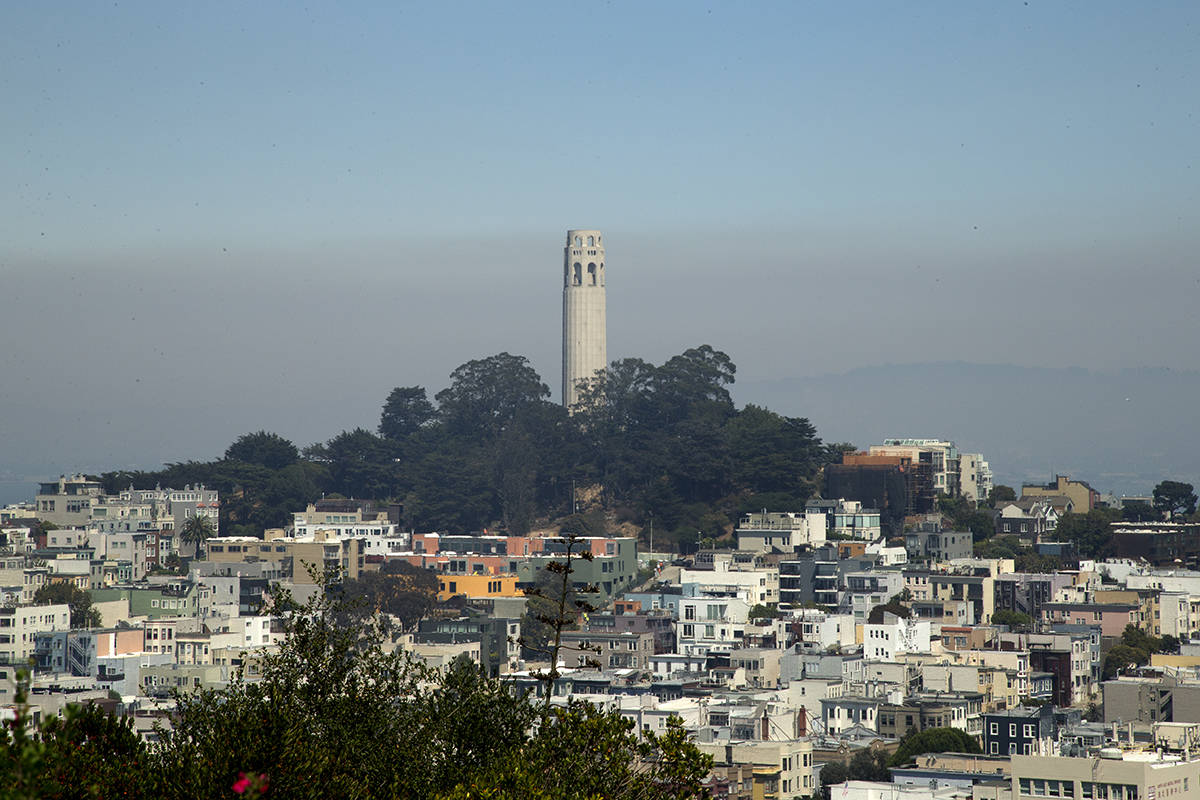 Smoke from numerous wildfires sits over the East Bay behind a view of Coit Tower from Ina Coolbrith Park on Wednesday, Aug. 19, 2020. (Kevin N. Hume/S.F. Examiner)
