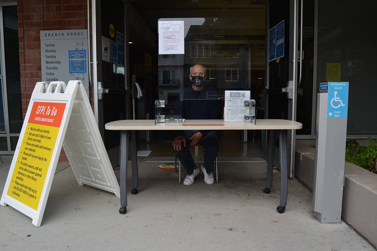 Library clerk Robert managed the pick-up table at the Marina Branch Library on Tuesday. (Samantha Laurey/Special to S.F. Examiner)