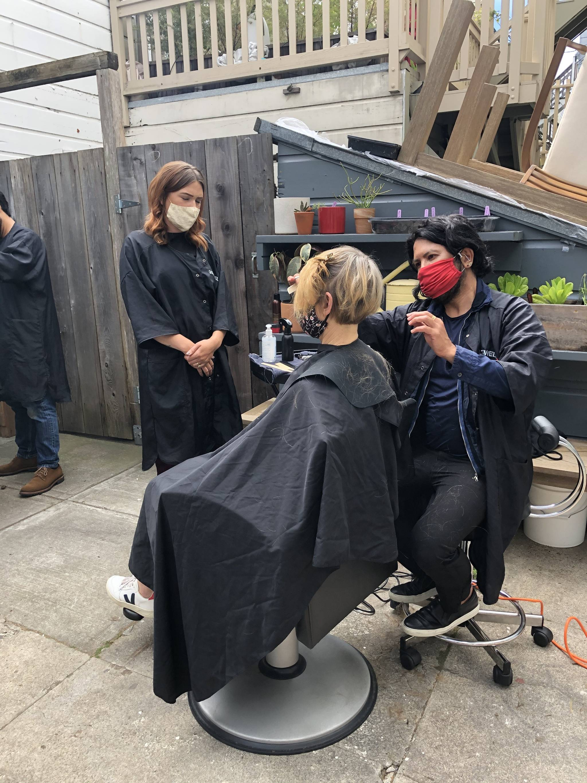 Hector Estrada, senior stylist at Studio Estrada, works with his assistant Regan Mellos on a client on the back patio. (Courtesy photo)