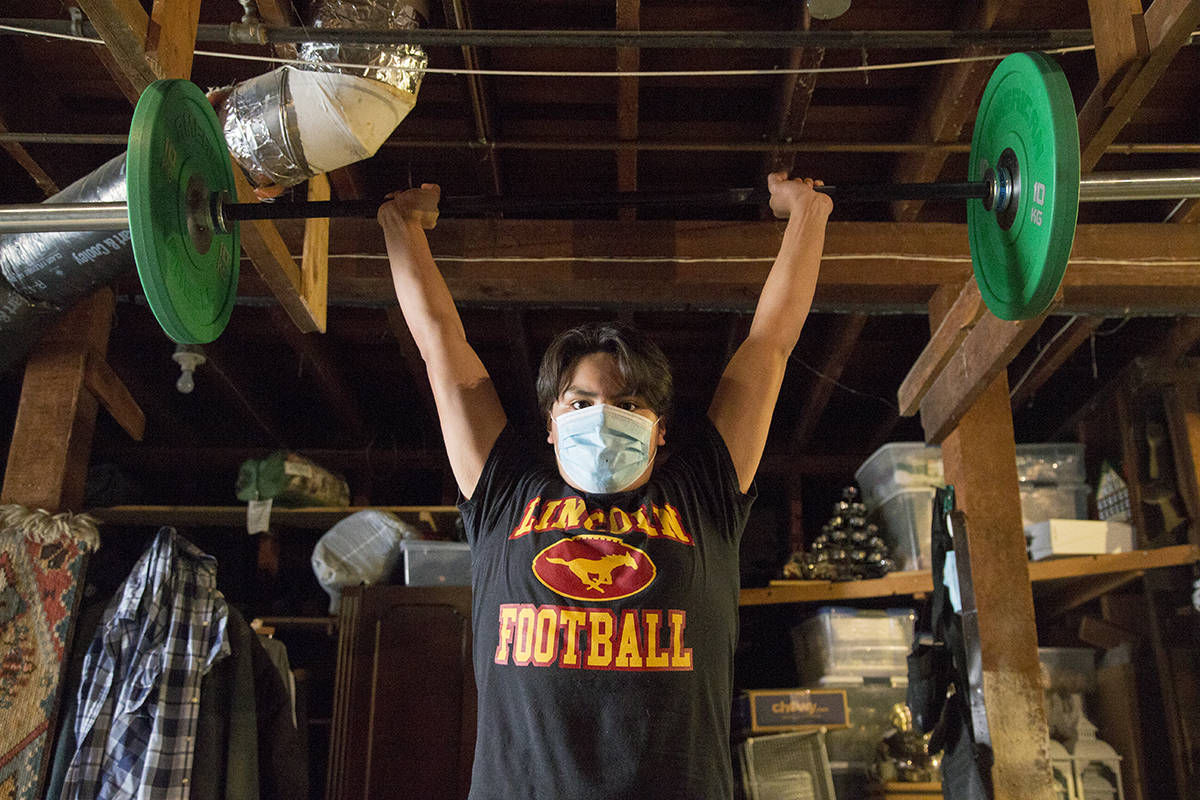 Andres Montoya, a member of the 2019 state champion Lincoln High football team, has been working out in his garage, anxiously anticipating the upcoming season. (Kevin N. Hume/S.F. Examiner)