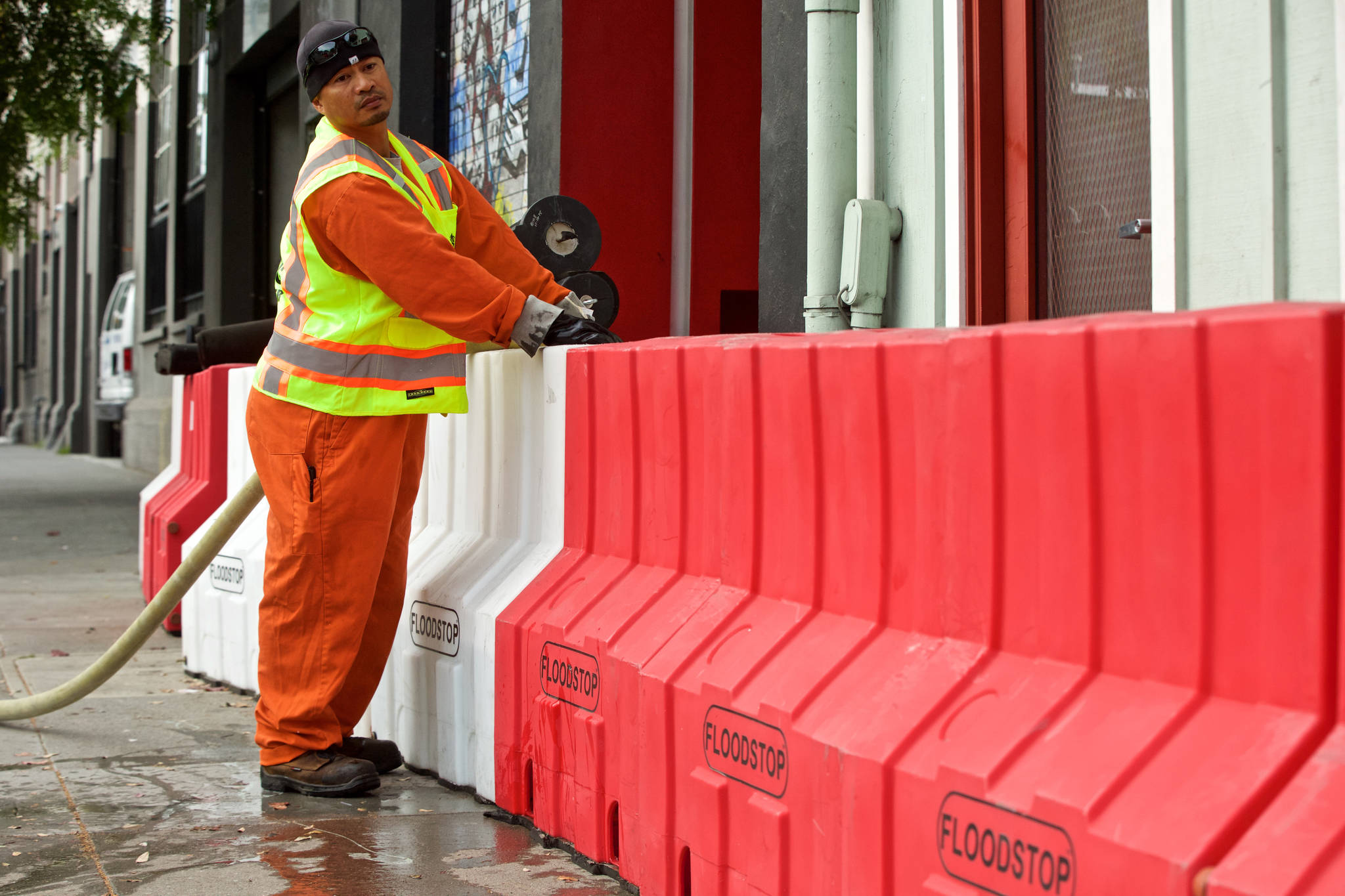 A San Francisco Public Utility Commission Wastewater employee fills flood barriers along Folsom Street near the intersection with 17th Street ahead of a forecasted strong storm. The area is one of several around The City with persistent flooding problems. (Kevin N. Hume/2018 S.F. Examiner)
