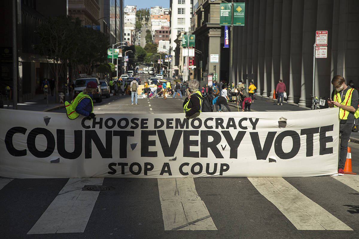 "Activists block off a section of Montgomery Street near the 555 California St. building, which is partially owned by the Trump Organization, to paint a street mural reading ""Count Every Vote,"" on Friday, Nov. 6, 2020. (Kevin N. Hume/S.F. Examiner)"