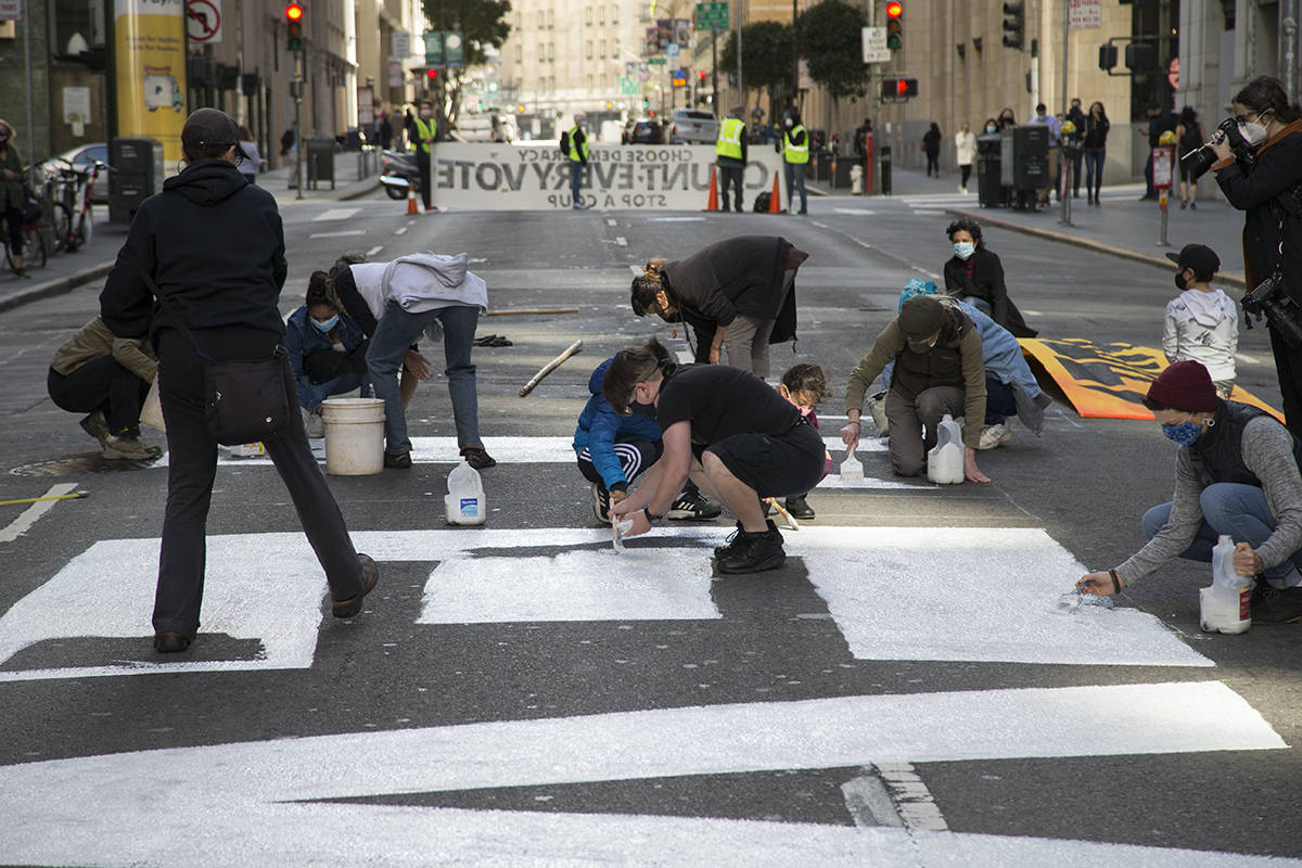"Activists paint a street mural reading ""Count Every Vote"" on a section of Montgomery Street near the 555 California St. building, which is partially owned by the Trump Organization, on Friday, Nov. 6, 2020. (Kevin N. Hume/S.F. Examiner)"
