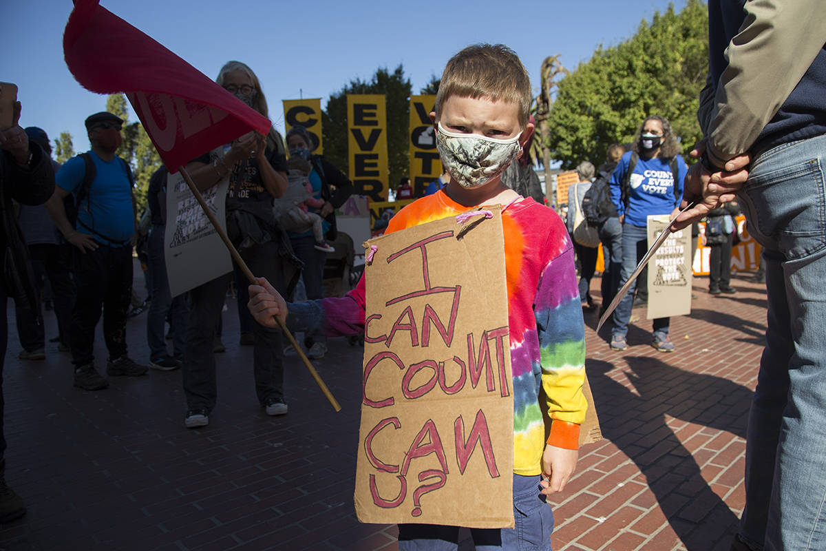 Oscar Gosling, 5, of Muir Beach wears a sign at the Embarcadero rally. (Kevin N. Hume/S.F. Examiner)