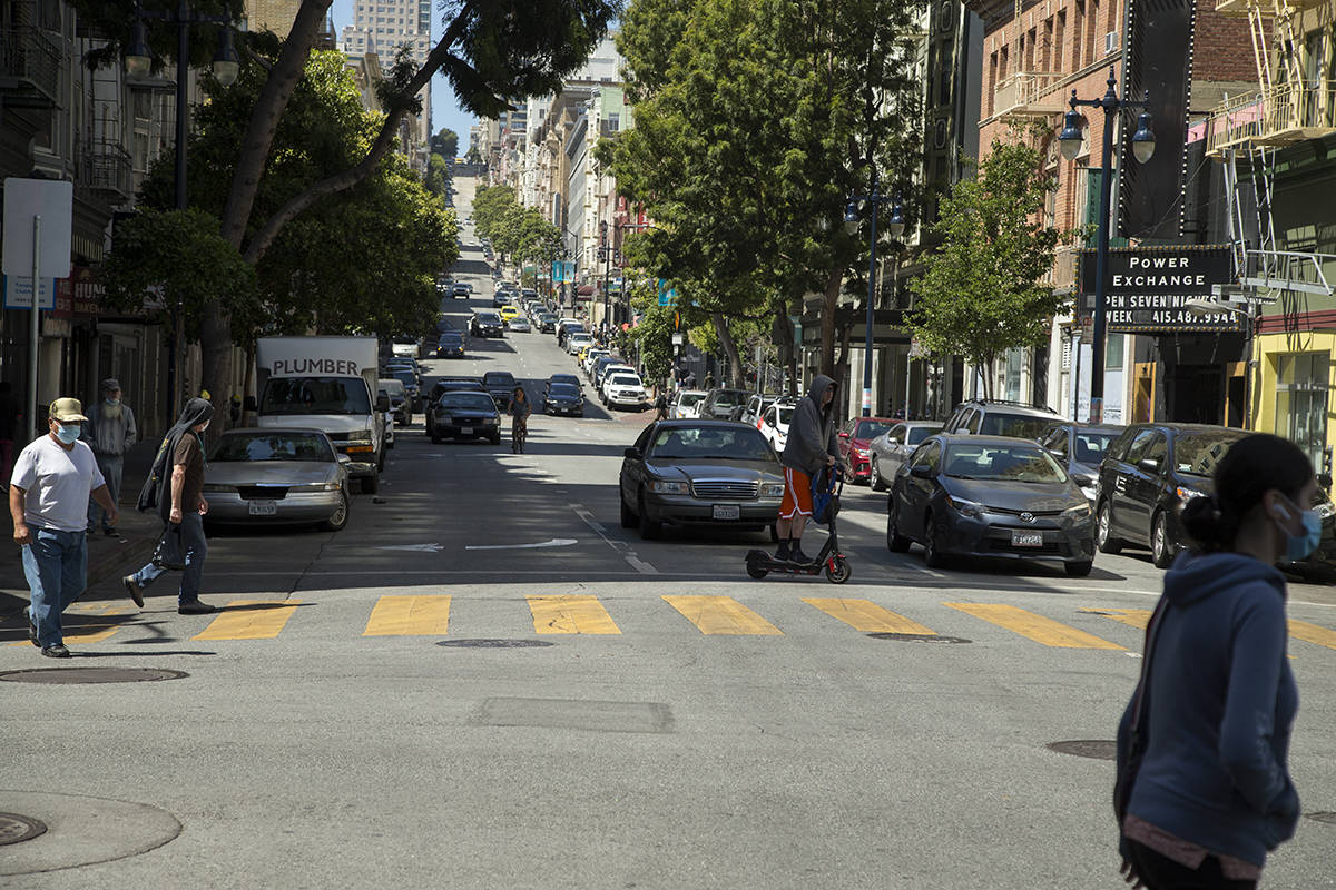 Pedestrians cross at Jones and Turk streets in the Tenderloin. (Kevin N. Hume/S.F. Examiner)