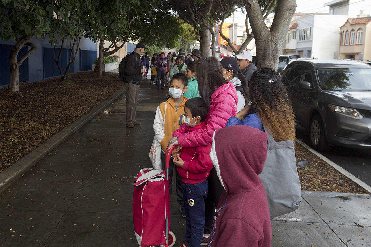 Families wait in line to pick up meals provided by the SF Unified School District at James Denman Middle School on Tuesday, March 17, 2020. (Kevin N. Hume/S.F. Examiner)