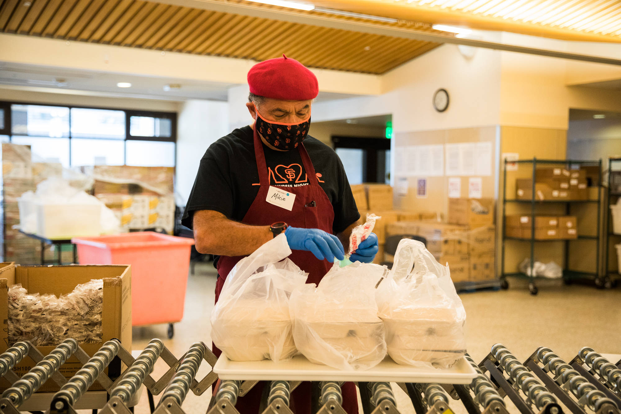 A volunteer prepares freshly cooked meals for curbside pickup at St. Anthony Foundation in the Tenderloin. (Photo by Ekevara Kitpowsong/Special to S.F. Examiner)