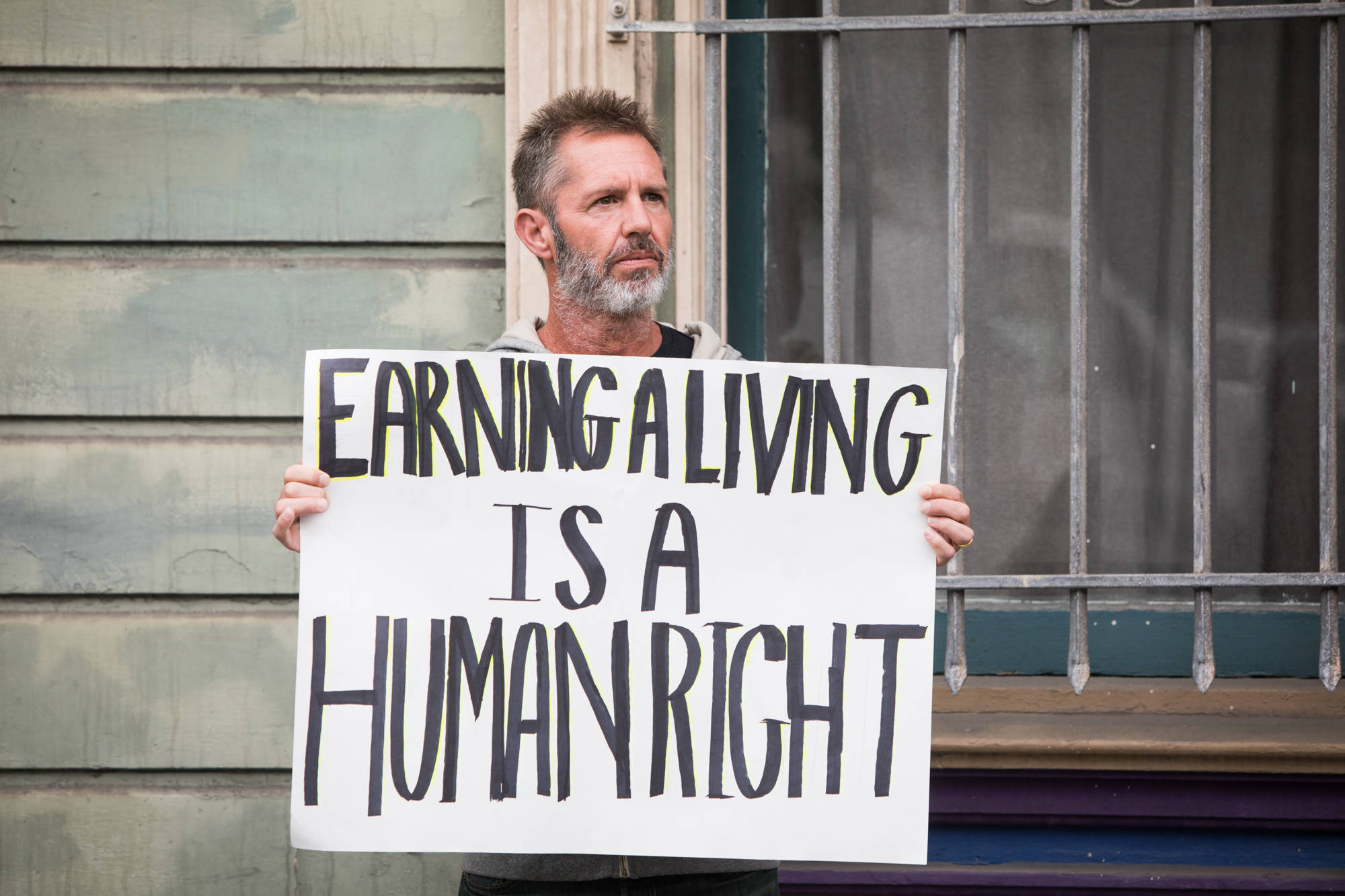 A man holds a sign during a protest of city COVID restrictions outside San Francisco Mayor London Breed's home in the Lower Haight on Sunday Dec. 13, 2020. (Photo by Ekevara Kitpowsong/Special to S.F. Examiner)