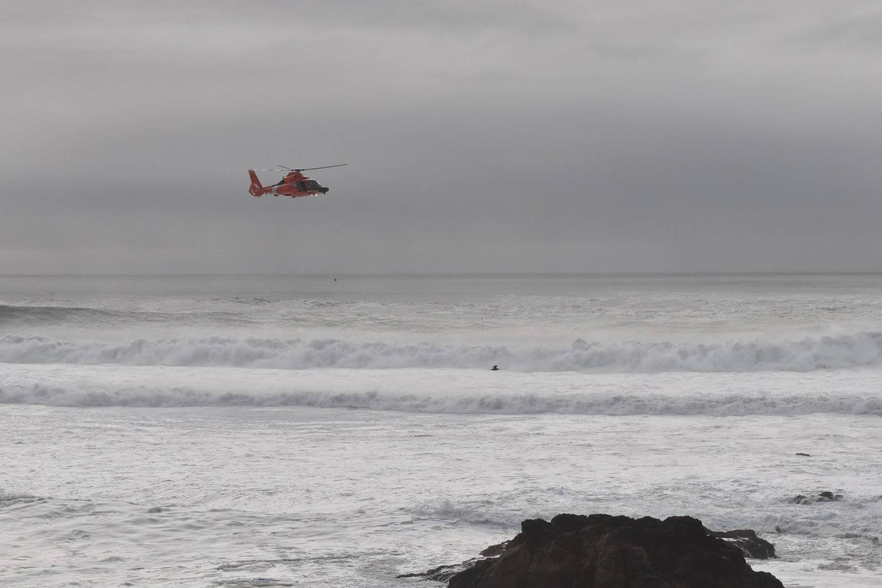 A rescue helicopter searched for a woman who was swept off the rocks at Pescadero State Beach Sunday afternoon. (Courtesy Cal Fire CZU)