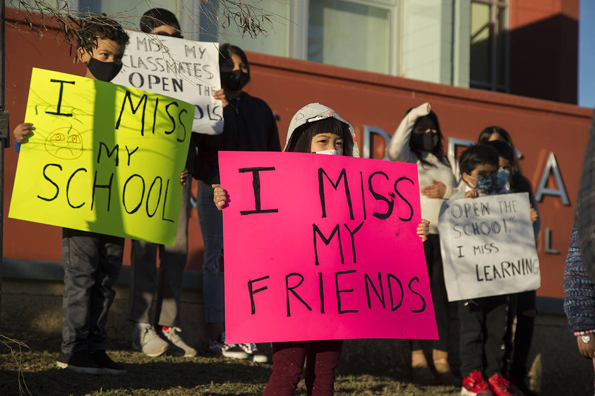 Children hold signs at Jose Ortega Elementary School during a news conference calling for the reopening of SFUSD schools on Thursday, Feb. 4, 2021. (Kevin N. Hume/S.F. Examiner)