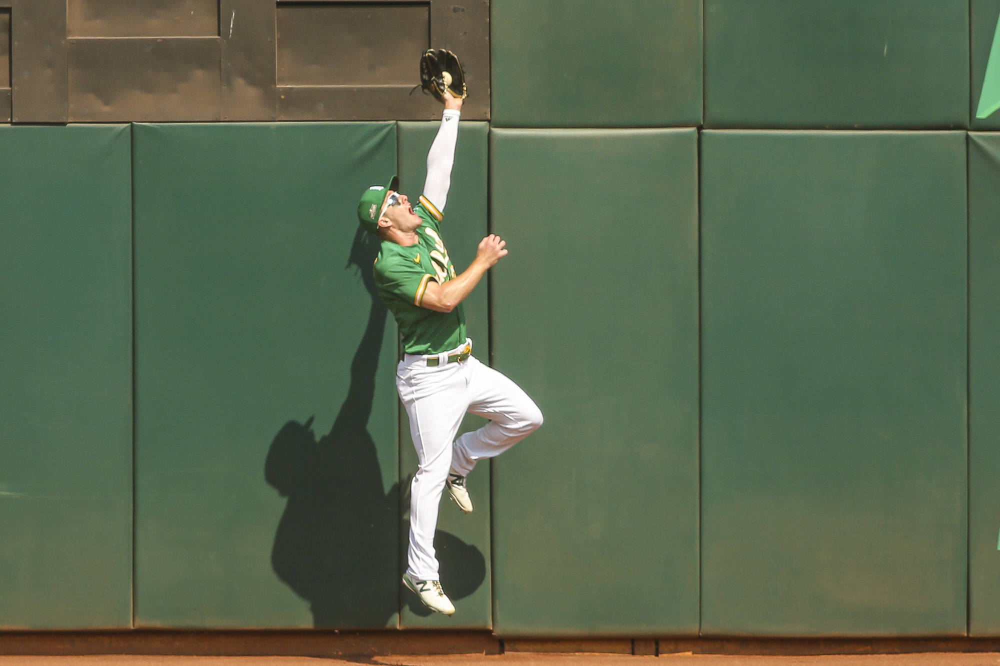 Oakland Athletics left fielder Mark Canha (20) steals a hit against the wall in Game 2 of the AL Wild Card Series against the Chicago White Sox on September 30, 2020 in Oakland, California. (Chris Victorio | Special to S.F. Examiner).