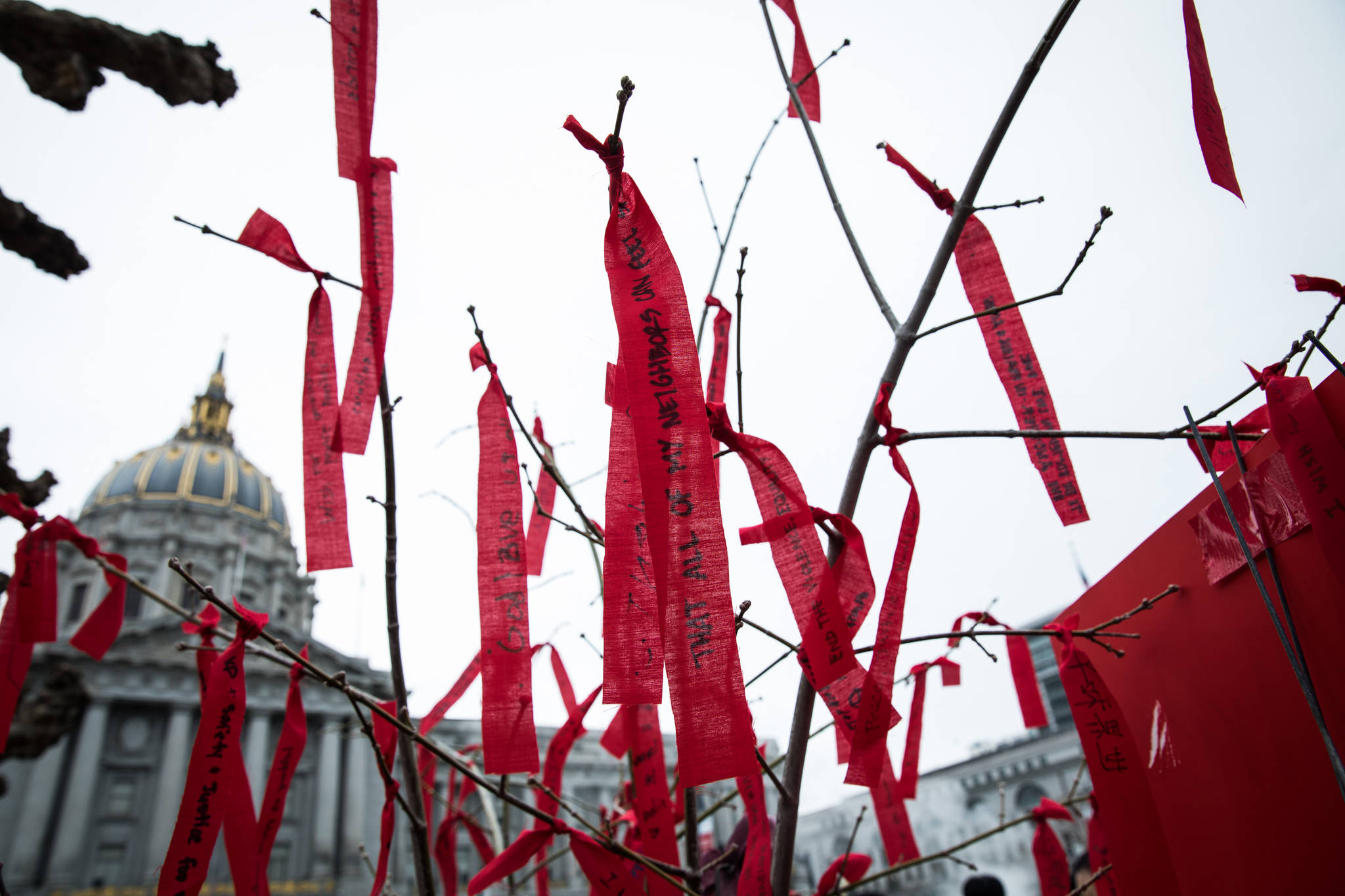People tied red ribbons to a Wish Tree at Civic Center Plaza during the Love Our People, Heal Our Communities SF event. (Photo by Ekevara Kitpowsong/ Special to S.F. Examiner)