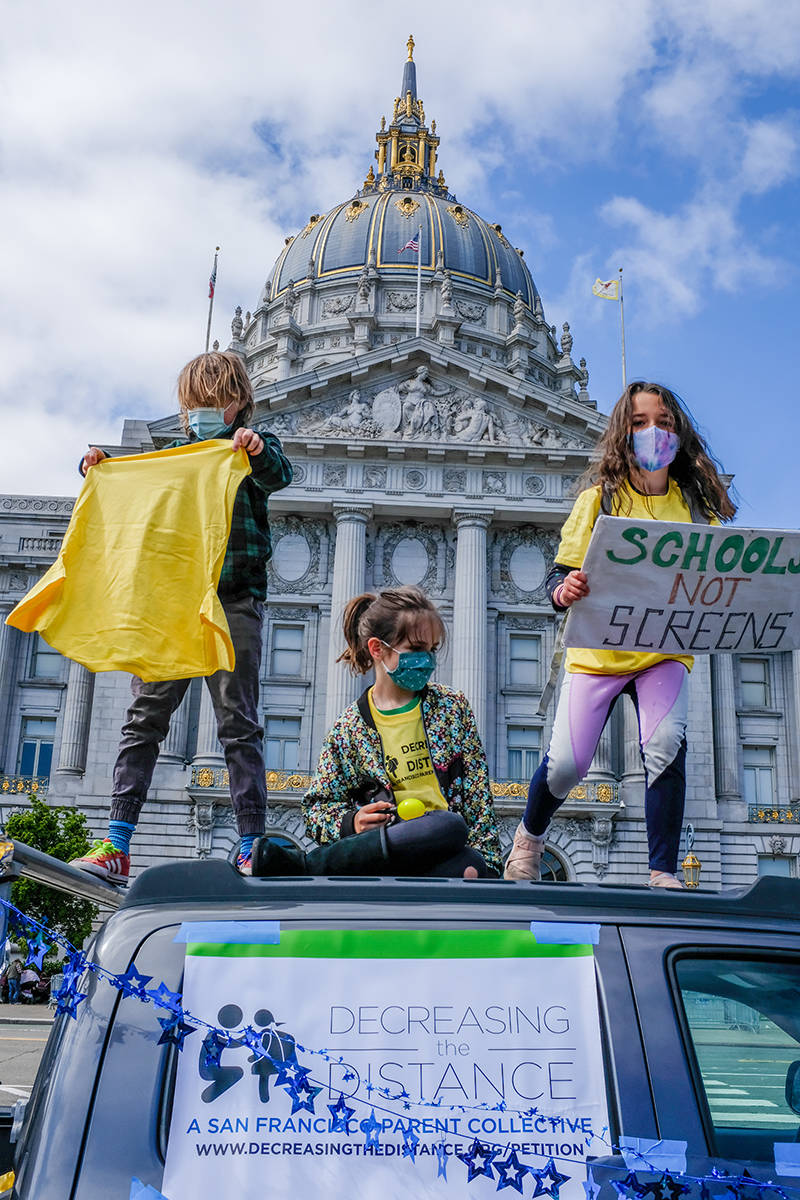Daclan O'Connor and friends dance atop the makeshift stage at the Decreasing the Distance protest at San Francisco City Hall. (By Camille Cohen/Special to the S.F. Examiner)
