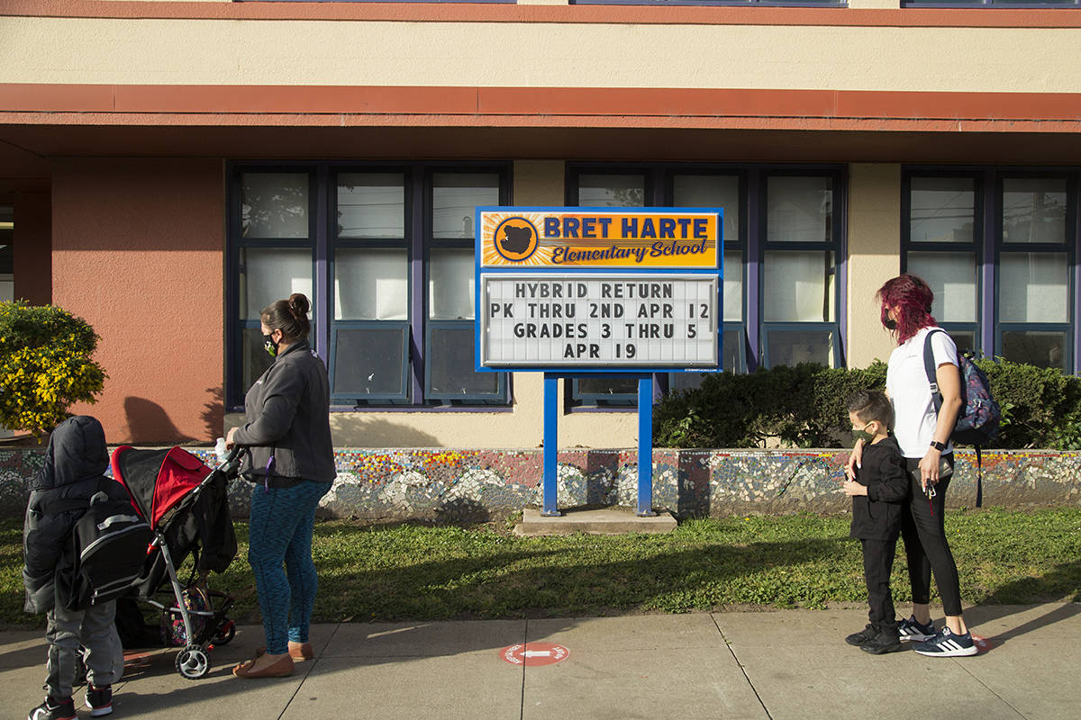 Parents and students wait in a socially distanced line before the first day of post-pandemic in-person learning at Bret Harte Elementary School on Monday, April 12, 2021. (Kevin N. Hume/S.F. Examiner)