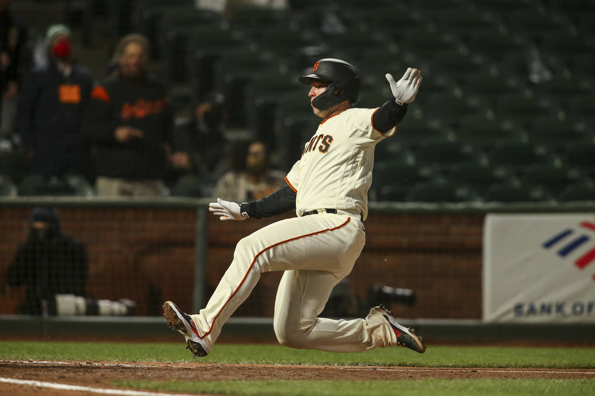 San Francisco Giants catcher Buster Posey (28) slides into home for the score on a triple by San Francisco Giants left fielder Austin Slater (13) in the 6th inning at Oracle Park on April 13, 2021 in San Francisco, California. (Photography by Chris Victorio | Special to the S.F. Examiner).