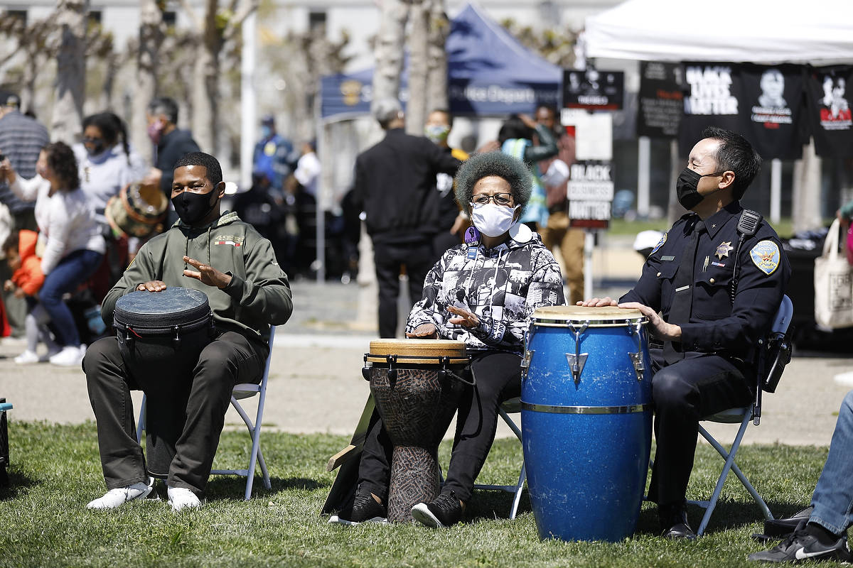 Police Chief Bill Scott (left), Mattie Scott of Healing4U.org, and Commander Daryl Fong take part in a drum circle. (CraigLee/Special to the S.F. Examiner)