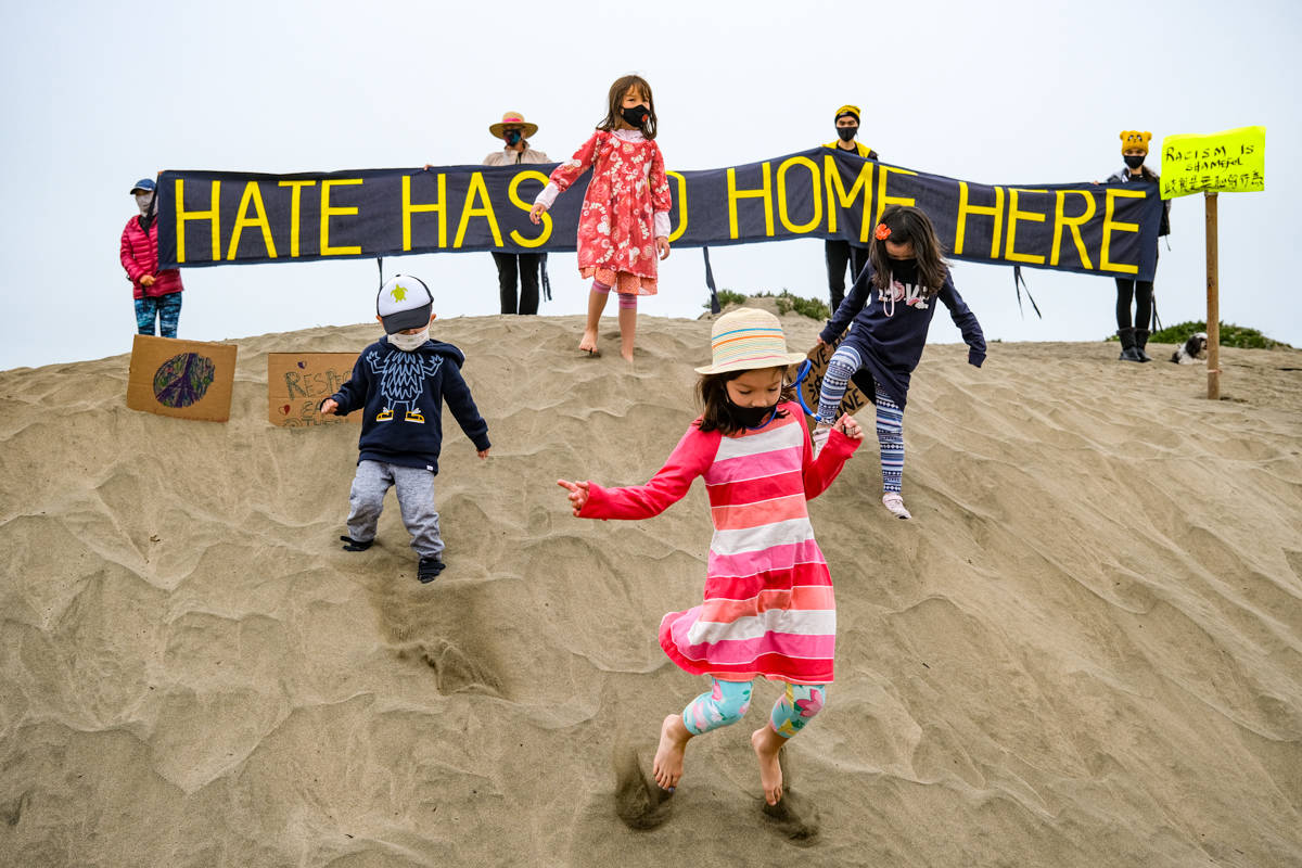 Kids play in front of CODEPINK's sign at the March for AAPI Solidarity and Safety on Sunday. (Camille Cohen / Special to SF Examiner)