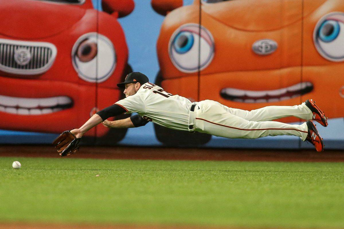 Austin Slater makes a dramatic play in the Giants vs. Reds game at Oracle Park in San Francisco on April 13, 2021. (Christopher Victorio/Special to S.F. Examiner)