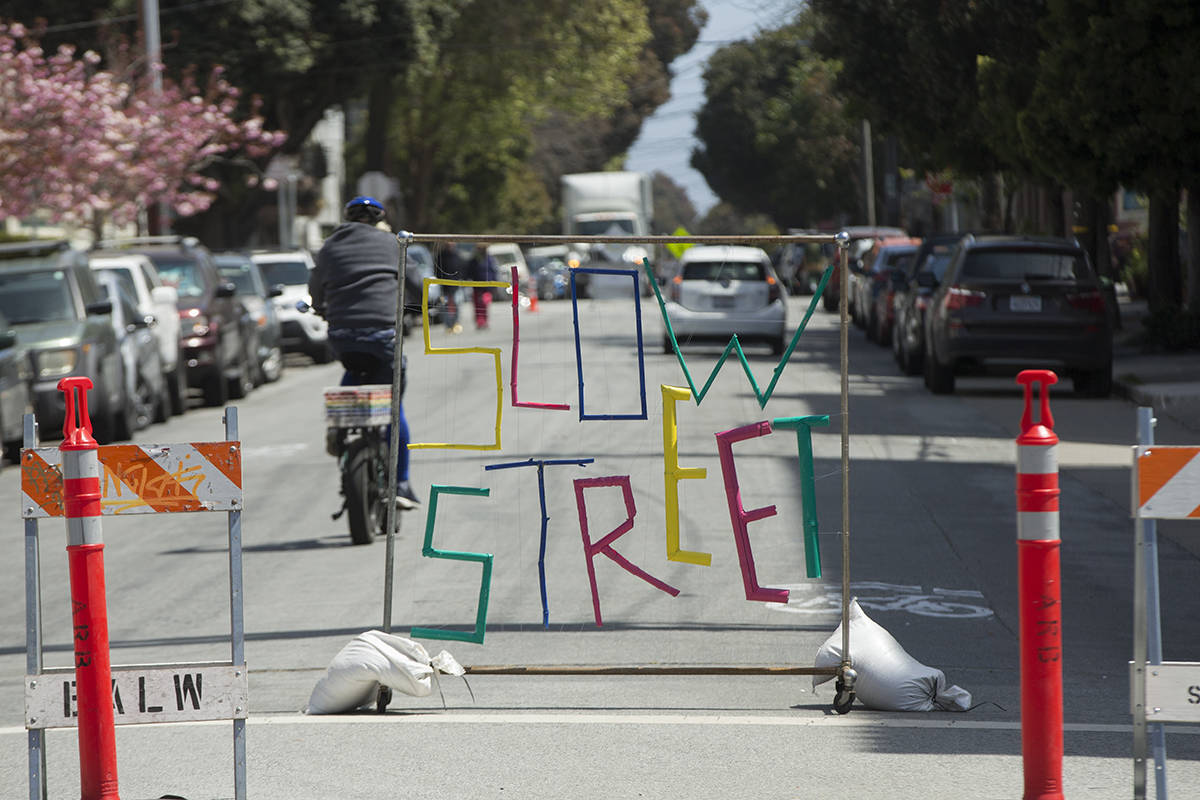 A cyclist heads past an artistic sign onto Page Street, a Slow Street, at Stanyan Street near Golden Gate Park on Monday, April 12, 2021. (Kevin N. Hume/S.F. Examiner)